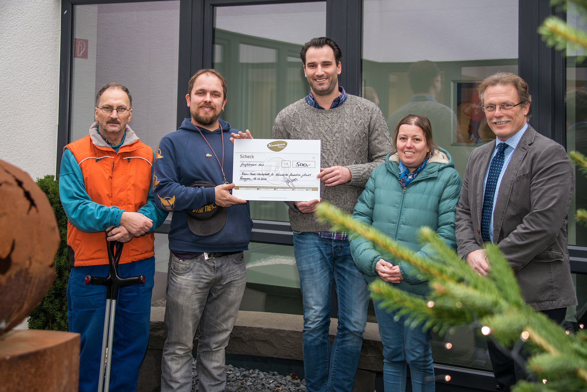 Patrik Tykesson (middle) presents the €500 check to the coworkers and manager of the Rhein-Mosel workshop, Mr. Thomas Hoffmann (right)